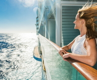 Happy woman looking at sea from a cruise ship