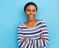 Happy young woman laughing against blue wall