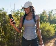 Hiker looking at smartphone while taking a break