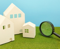Houses and magnifying glass on green grass