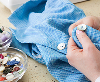 hands sewing button