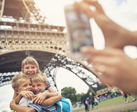Kids tourists smiling at the camera near Eiffel Tower