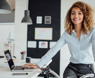 Latina Businesswoman Using Laptop In Her Office