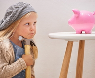 Little girl looking at piggy bank