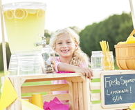 Little girl sitting behind her lemonade stand