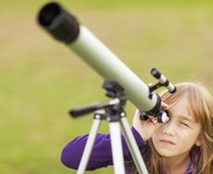 Little girl using best telescope to stargaze