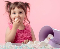 Little girl with marshmallow on pink background