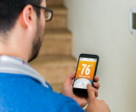 Male homeowner uses smartphone to control thermostat