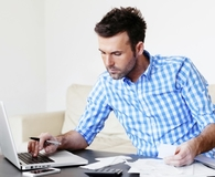 Man adding up his debt during debt reduction plan
