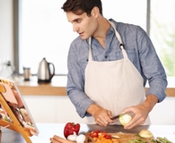 Man using best cookbooks while cooking