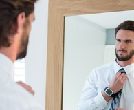 Man getting dressed in bedroom while looking at mirror