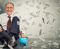 Man sitting on floor with piggy bank under money rain