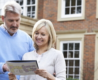 Mature Couple Standing Outside House