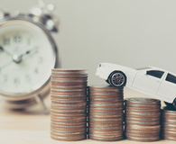Miniature car on money coin stack growth with clock