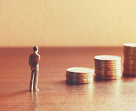 Miniature people looking future with stack coin