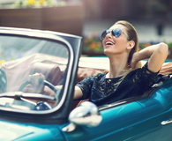 Model in sunglasses sitting in luxury retro car