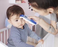 Mom using best forehead thermometers to see if son is sick