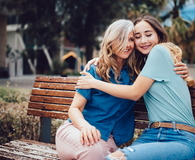 Mother and daughter embracing while sitting on a bench