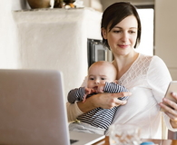 Mother at home with baby working on laptop