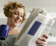 Woman reading newspaper through subscription that's worth the money