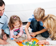 Parents playing board game with their children