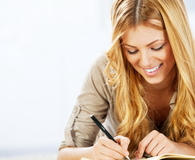 Portrait of a cheerful blonde woman writing diary