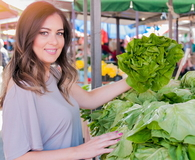 Portrait of beautiful young woman choosing green leafy vegetables