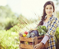 Portrait of woman carrying vegetables in crate at farm