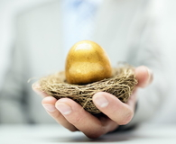 Retirement savings golden nest egg in businessman hand