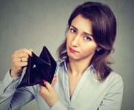 Sad businesswoman holding empty wallet