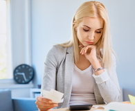 Sad young woman counting bills