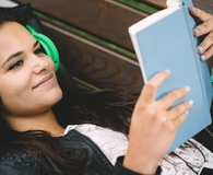 Schoolgirl with headphones and book resting on bench
