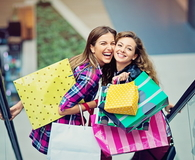 Shopping girls are laughing on the escalator