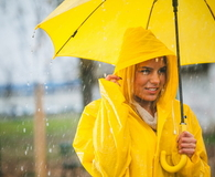 Smile woman holding yellow umbrella on rainy day