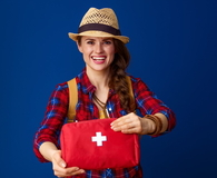 Smiling healthy traveler woman showing first-aid kit