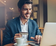 Smiling man with credit card and laptop