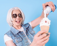 Smiling senior woman adding cream in ice cream