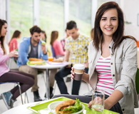 Smiling student on lunch break in cafeteria looking at camera