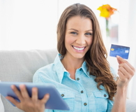 Smiling woman holding tablet and showing her credit card