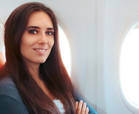 Smiling Woman Sitting By the Window on An Airplane