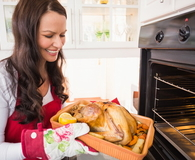 Smiling woman taking out her roast turkey