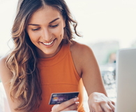 Smiling woman with credit card and laptop