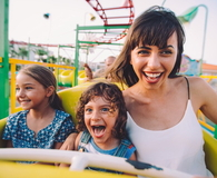 Son and daughter with mother on roller coaster ride