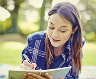 Student writing in diary while lying at park