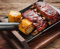 Tasty char grilled ribs served on wood background
