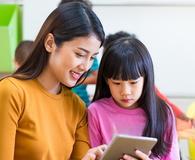 Teacher teach girl student with tablet computer