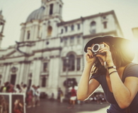 Tourist woman photographing with digital camera in Rome
