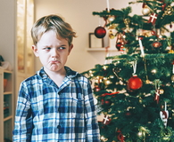 Unhappy boy stands before chistmas tree