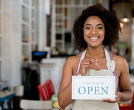 Waitress holding an open sign at a restaurant