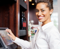 Waitress Preparing Bill At Cash Register In Restaurant